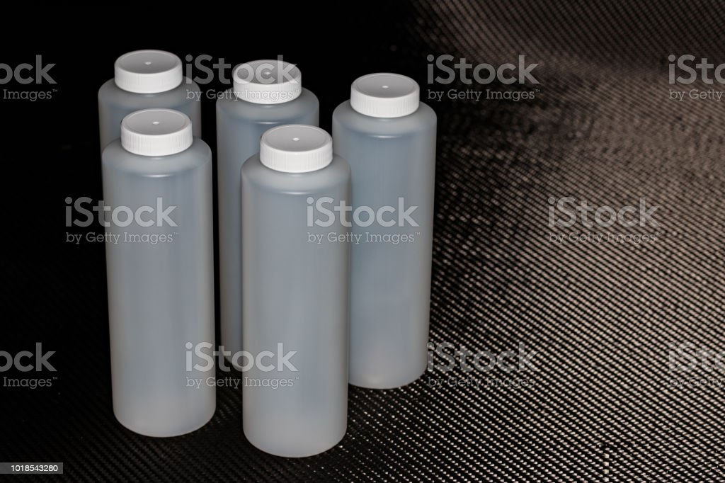 White plastic containers with lids on carbon fiber stock photo