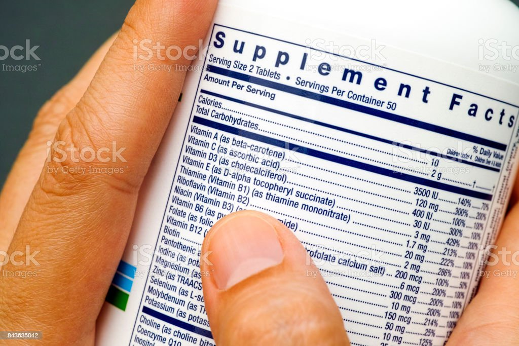White plastic jar with supplement facts of multivitamins in woman hands. stock photo