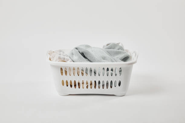 White plastic laundry basket with dirty clothes on grey White plastic laundry basket with dirty clothes on grey laundry basket stock pictures, royalty-free photos & images