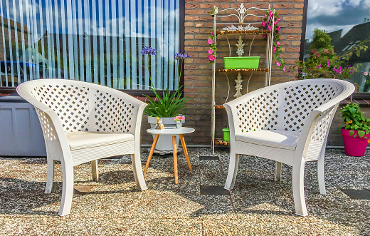 white plastic lounge chairs with a small wooden table and garden decorations in the backyard at home