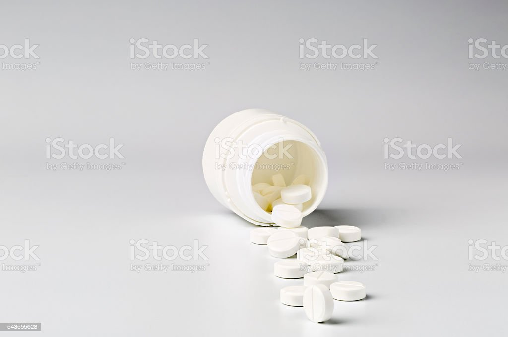 White plastic pill bottle and heap of round pills stock photo