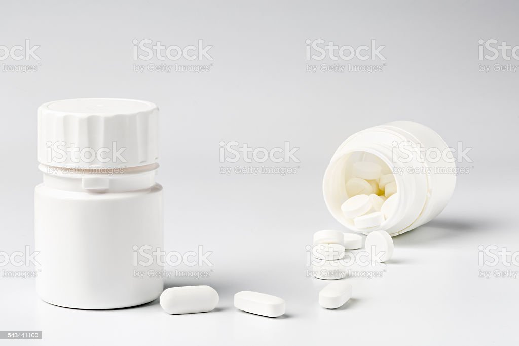 White plastic pill bottles and heap of various pills stock photo