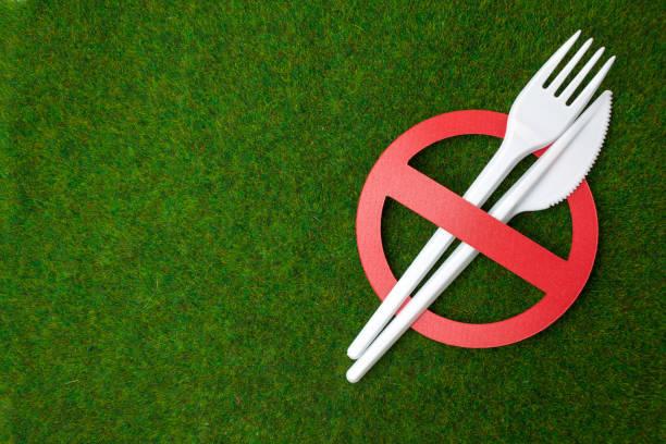 Weißes Plastikgeschirr auf einem Grashintergrund als Symbol für Umweltverschmutzung. Verbot von Einzelgebrauch-Kunststoff. – Foto