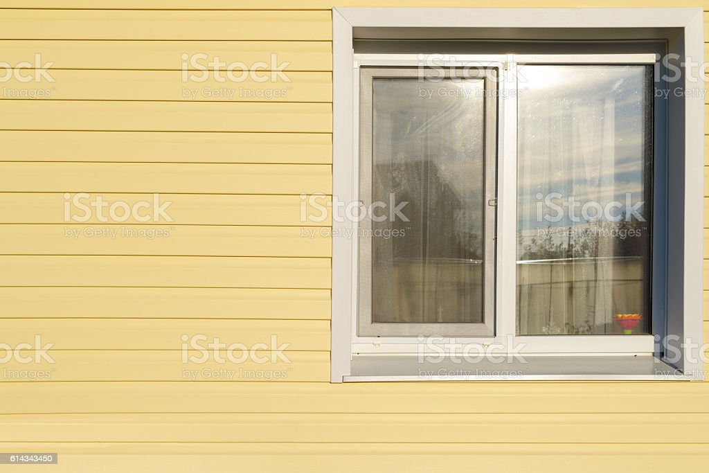 white plastic window on the wall lined with yellow siding stock photo