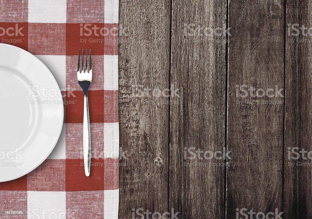 white plate and fork on old wooden table stock photo