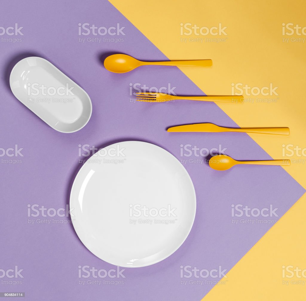 White plate and yellow cutlery on a pastel yellow-lilac background. Colors in the style of pop. stock photo