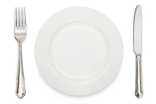 A white plate, knife and fork against a white background stock photo