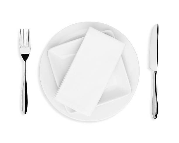 White plate, napkin, knife and fork on white background stock photo