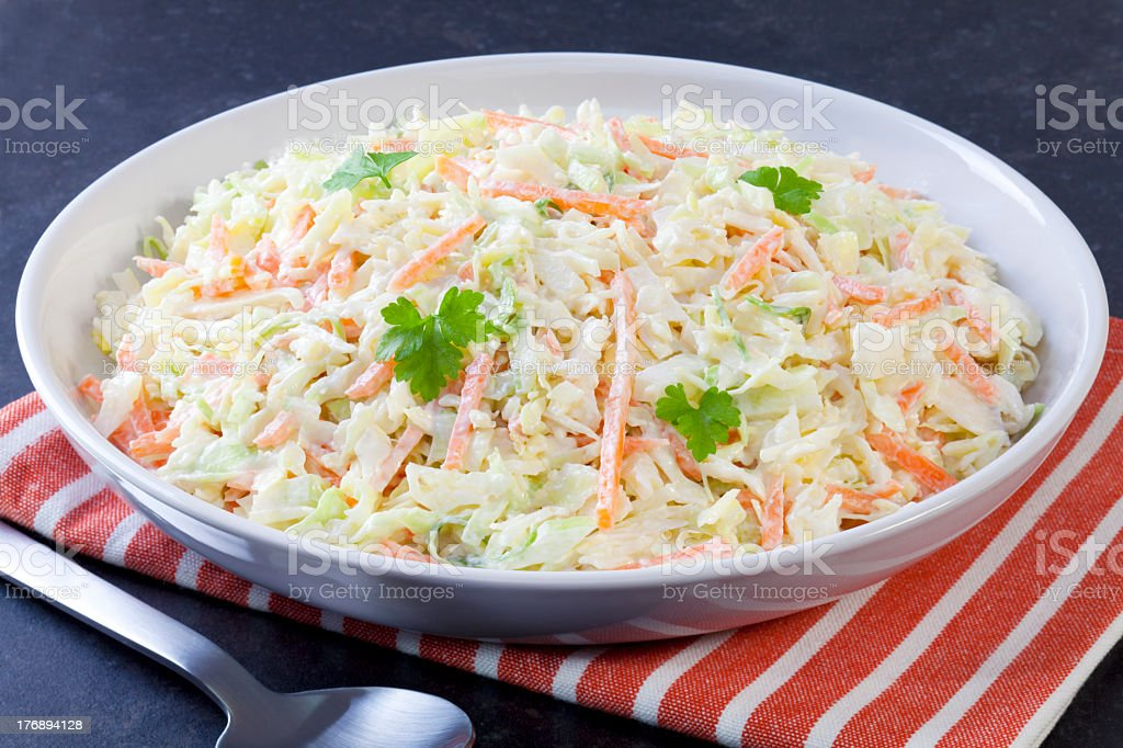 White plate of coleslaw with cloth and spoon on dark surface stock photo