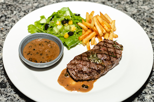 A White Plate of Medium Rare Beefsteak served with French Fried and Salad