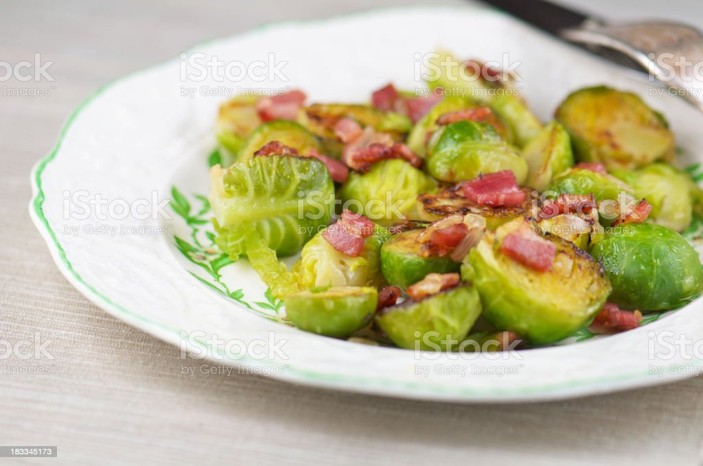 White Plate of Sauteed Brussels Sprouts with Bacon royalty-free stock photo