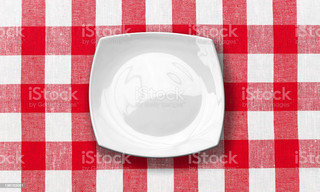 white plate on red checked fabric tablecloth stock photo