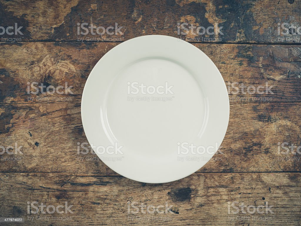 White plate on wooden table stock photo