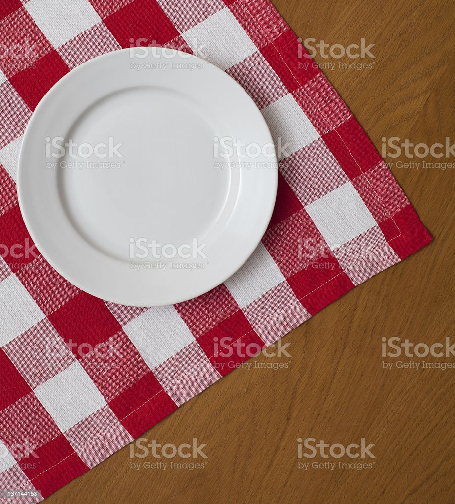 white plate on wooden table with red gingham tablecloth stock photo