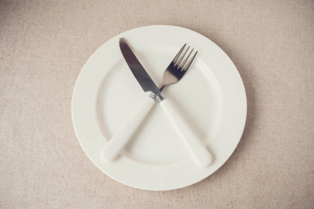 white plate with knife and fork, Intermittent fasting concept, ketogenic diet, weight loss stock photo
