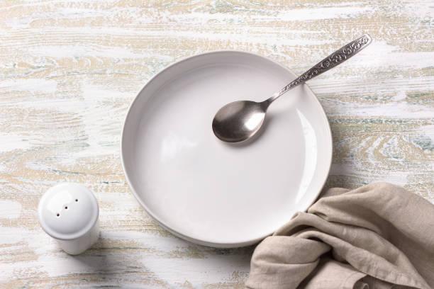 Weiße Platte mit Leinenserviette auf weißem Holzhintergrund – Foto