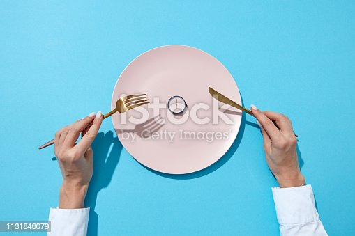 Round watch of six o'clock and woman's hand with fork and knite in agirl's hands on a blue background with shadows. Time to lose weight, eating control or diet concept. Place for text.
