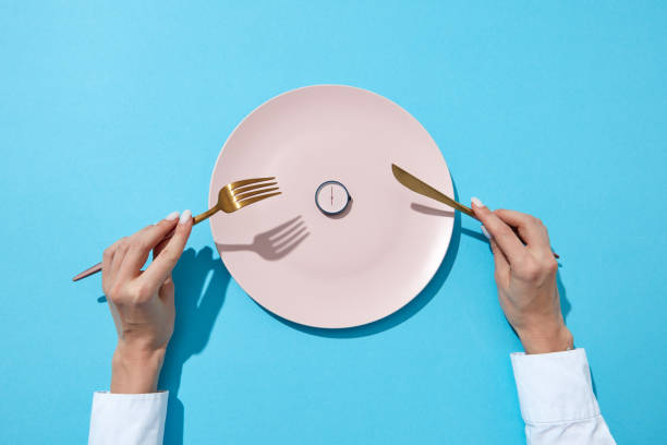 White plate with round whatch shows six o'clock served knife and fork in a girl's hands on a blue background. Time to eat and diet concept. Top view. stock photo
