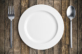 Dinner place setting. A white plate with silver fork and spoon  on wood background.