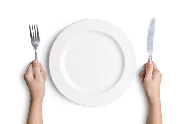 White plate with silver fork and spoon Dinner place setting. A white plate with silver fork and spoon isolated on white background with clipping path hungry stock pictures, royalty-free photos & images
