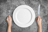 Dinner place setting. A white plate with silver fork and spoon isolated on cement background with clipping path