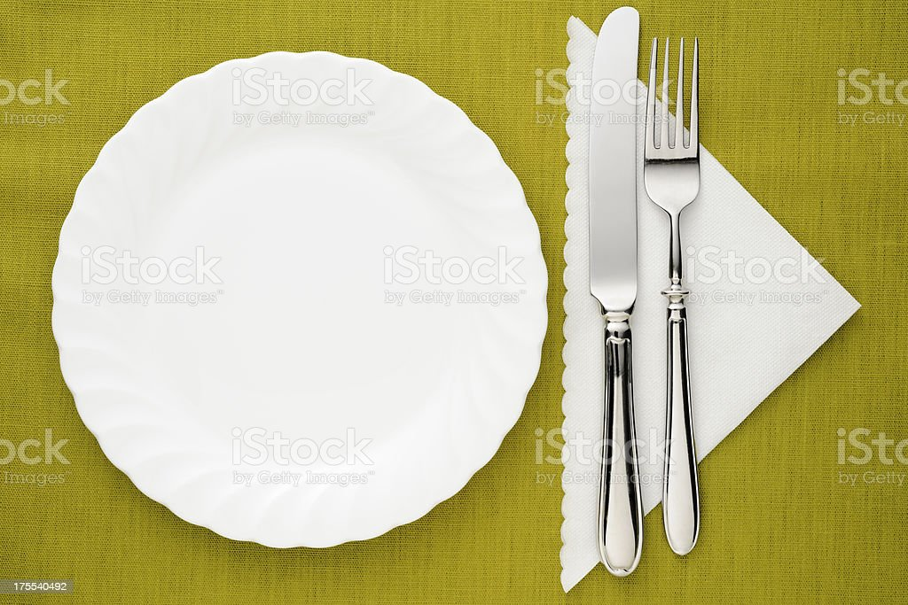White plate with silver knife and fork on green tablecloth stock photo