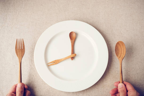 white plate with spoon and fork, Intermittent fasting concept, ketogenic diet, weight loss stock photo