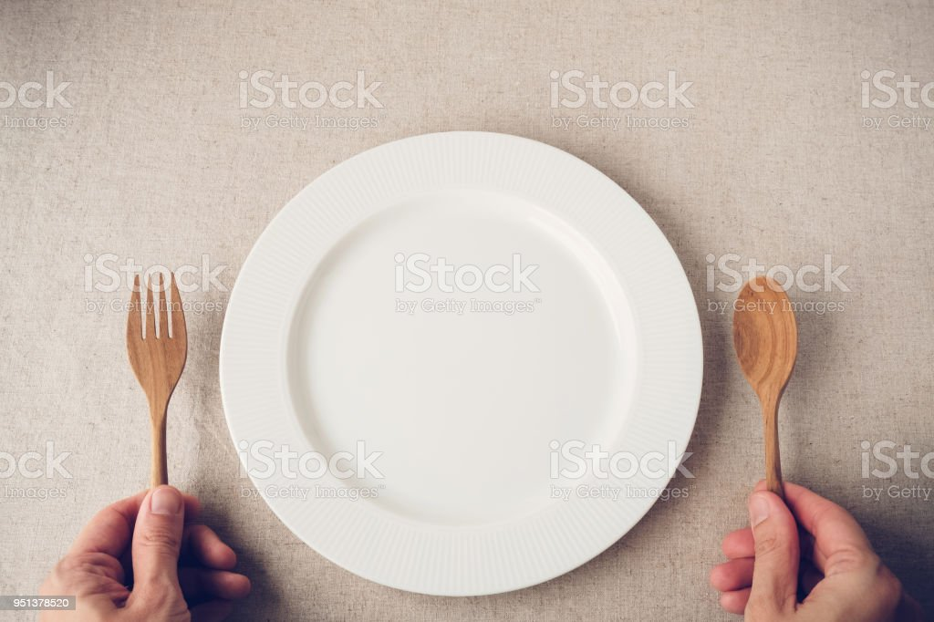white plate with spoon and fork, Intermittent fasting concept, ketogenic diet, weight loss, diet stock photo