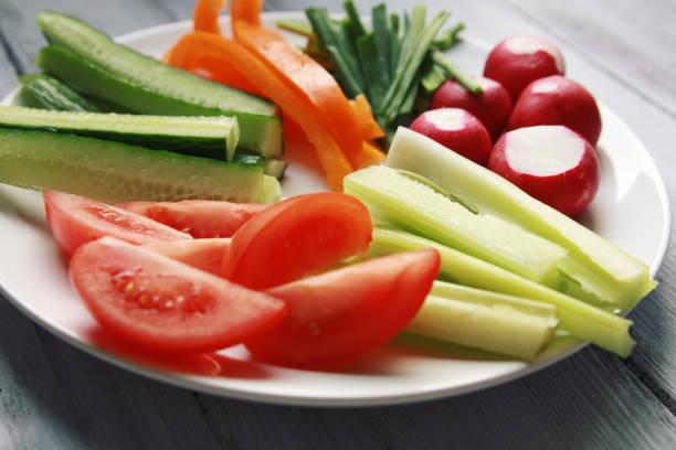 Weißen Teller mit Gemüse für eine vegane Salat – Foto