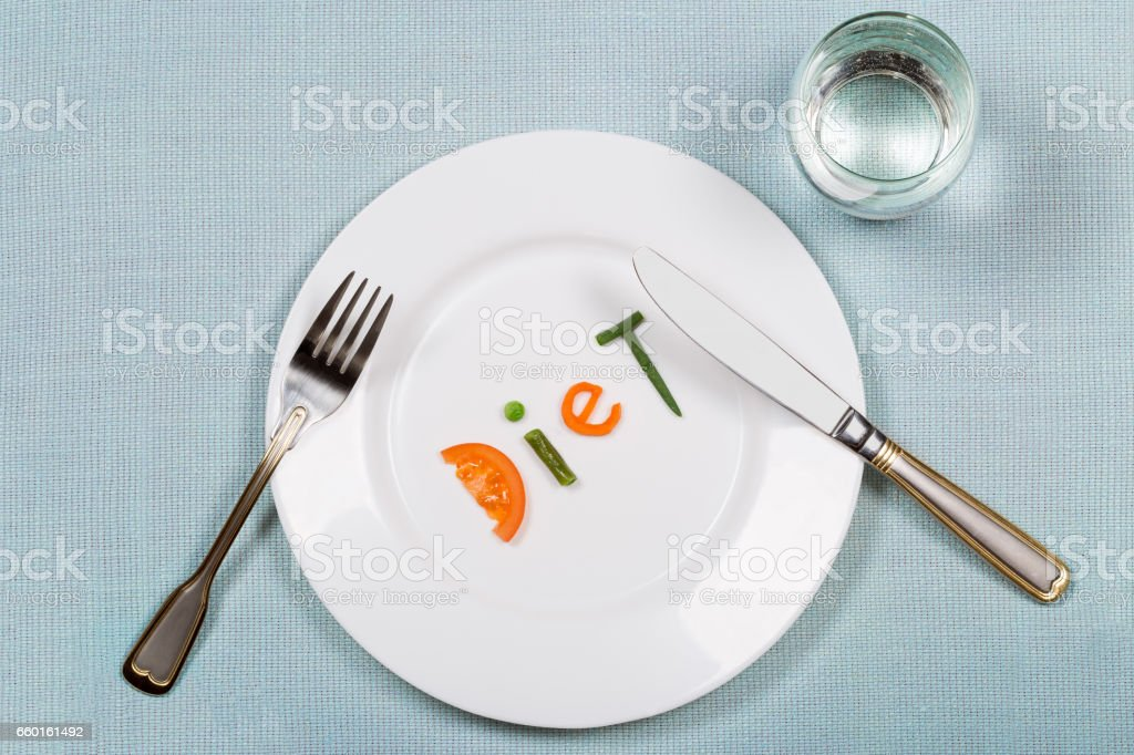 White plate with word diet made of pieces of vegetables and glass of water. stock photo