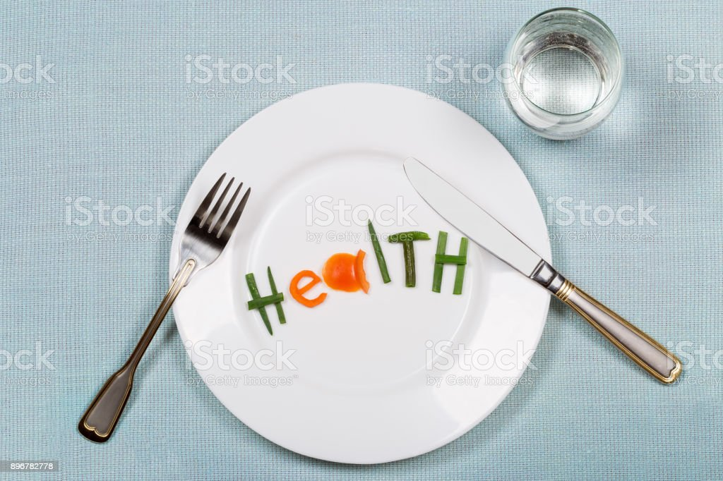 White plate with word health made of colorful pieces of vegetables and glass of pure on blue teblecloth background. Flat lay. Top view. stock photo