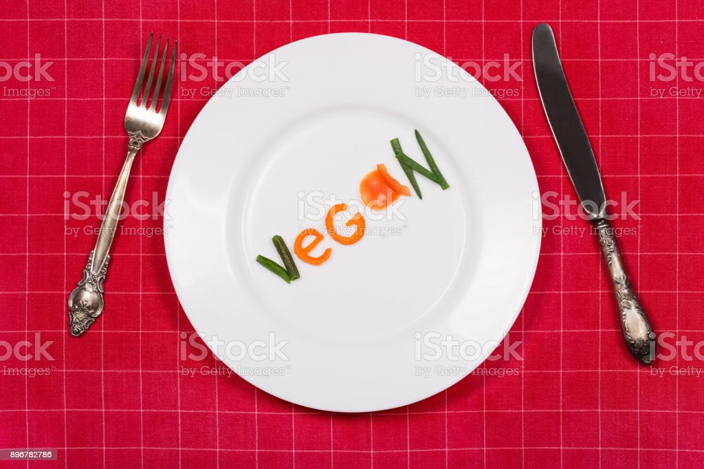 White plate with word vegan made of pieces of vegetables on red tablecloth background. Vintage fork and knife near it. Flat lay. Top view. stock photo