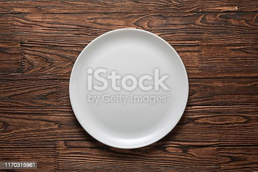 Empty white plate on a wooden table.
