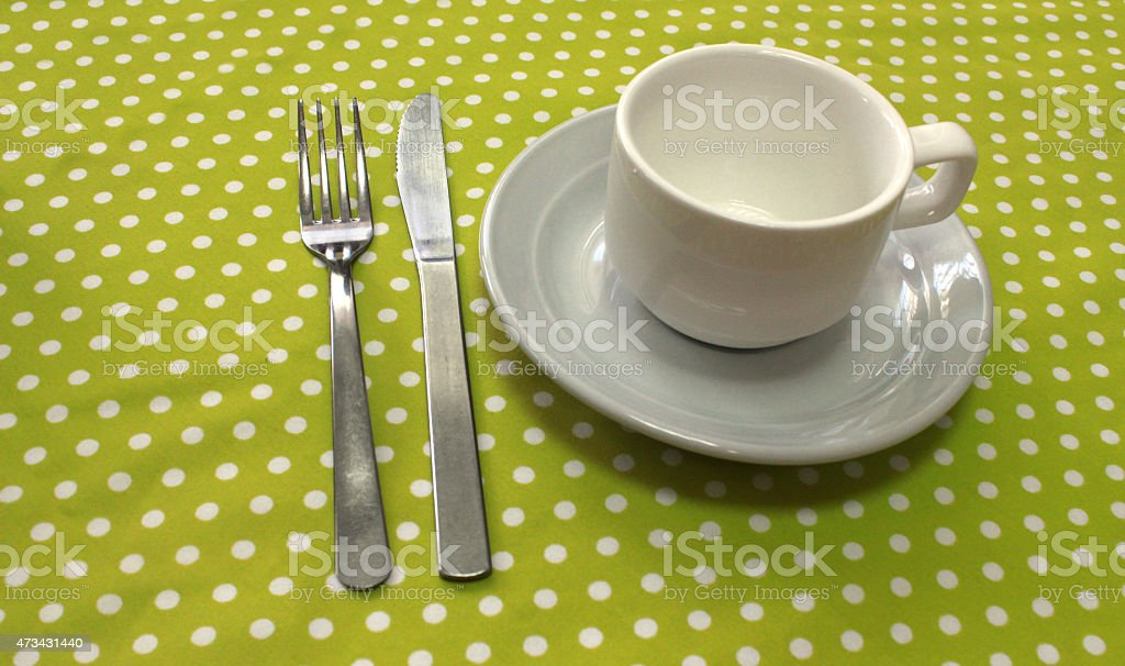 White plates and cup, fork and knife on tablecloth stock photo
