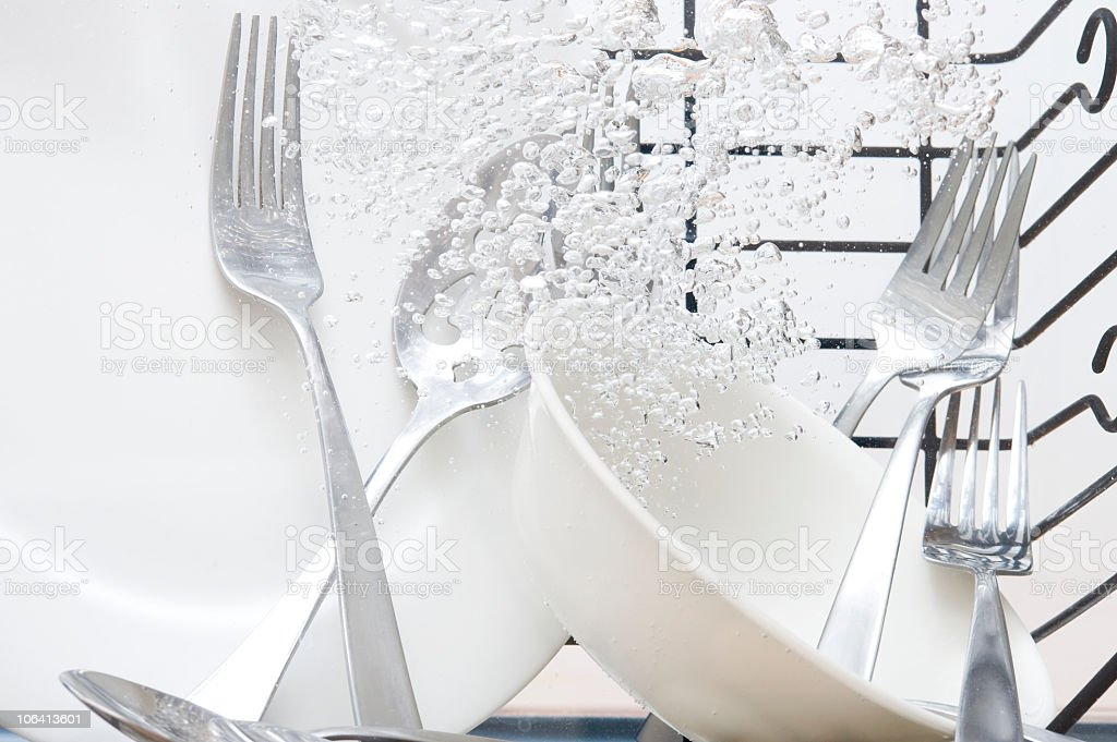 White plates and silverware underwater in a dishwasher stock photo