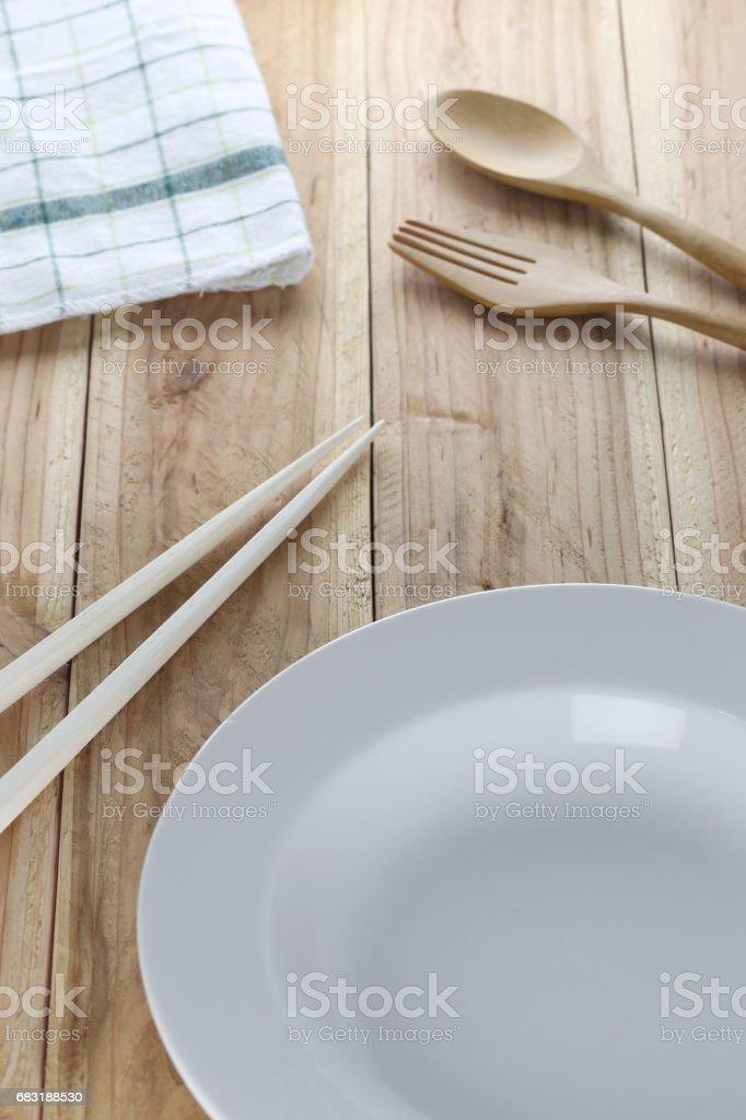 흰 접시, 나무로 되는 숟가락 및 젓가락 나무 바닥 배경. royalty-free 스톡 사진