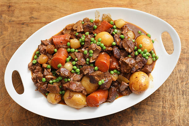 White Platter Full Of Beef Stew An overhead horizontal photograph of a white serving platter full of savory beef stew on a grungy wooden background. beef stew stock pictures, royalty-free photos & images