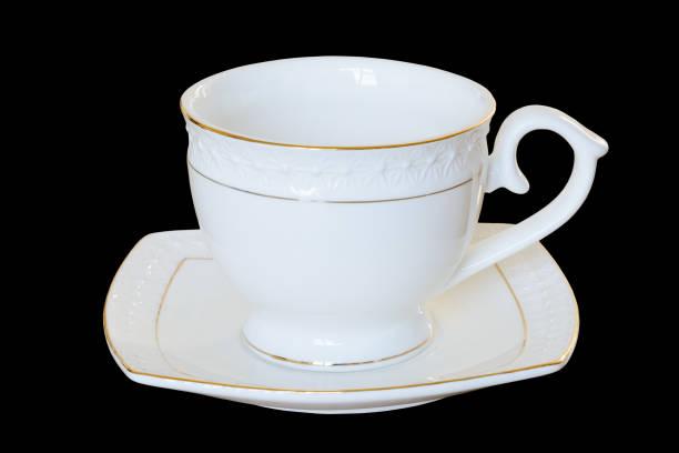 weißes porzellantasse mit untertasse für tee oder kaffee, demitasse oder teetasse. isoliert, schwarzer hintergrund. - mokkatassen stock-fotos und bilder