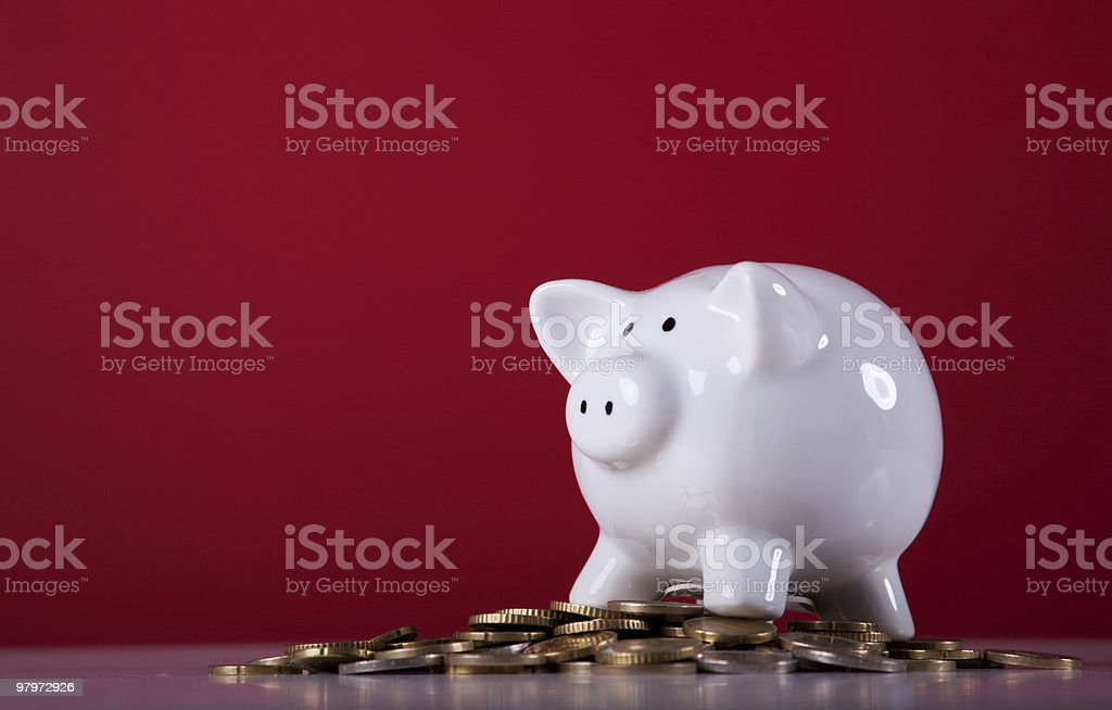 White porcelain piggy bank on top of some coins royalty-free stock photo