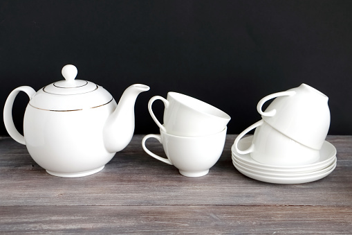 White porcelain tea cups with teapot on a table.