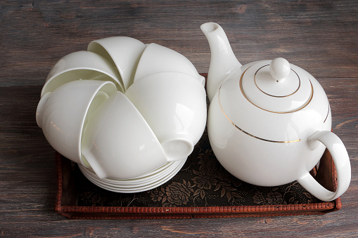 White porcelain tea set on a wooden tray