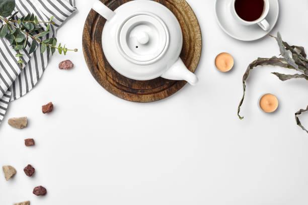 eine weiße porzellan teekanne auf einem holzbrett und eine weiße tasse mit tee auf dem tisch. ansicht von oben. textfreiraum - keramikteekannen stock-fotos und bilder