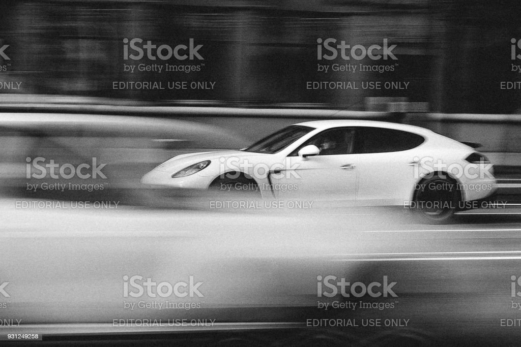 White Porsche Panamera in Motion Minsk, Belarus - April 15, 2017: White Porsche Panamera in Motion at Intensive Traffic on Independence Avenue. Speed. Motion blur shot. Editorial Black and White photo. 2017 Stock Photo