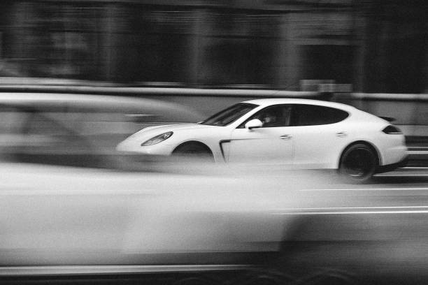 White Porsche Panamera in Motion Minsk, Belarus - April 15, 2017: White Porsche Panamera in Motion at Intensive Traffic on Independence Avenue. Speed. Motion blur shot. Editorial Black and White photo. porsche stock pictures, royalty-free photos & images