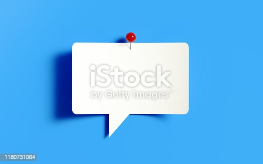 White post it note pinned with a red push pin on blue background. Horizontal composition with copy space.