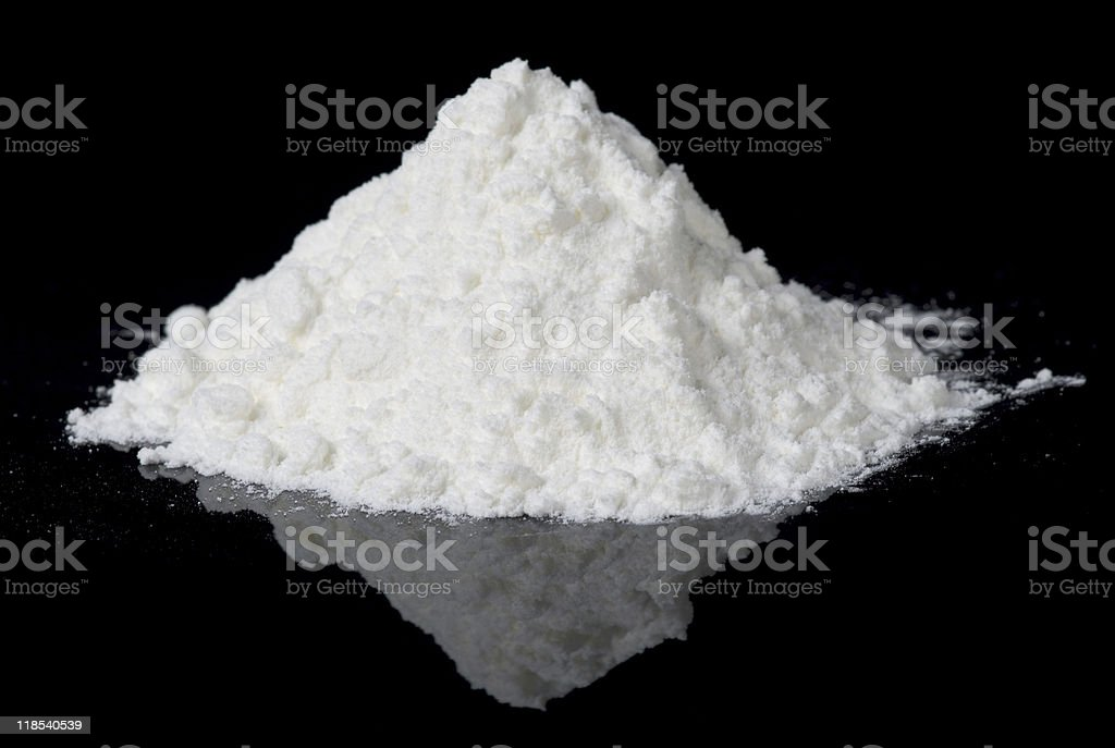 White powder on black reflective surface stock photo