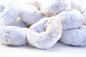 White powdered sugar donuts on white background