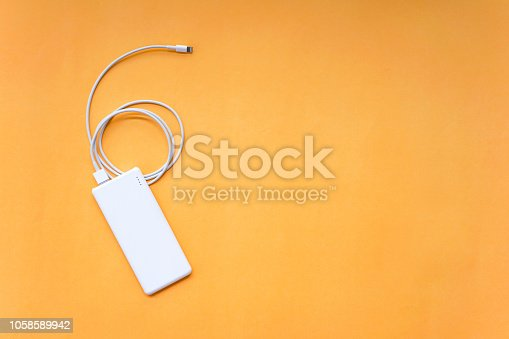 White Power Bank with USB Cable Isolated on Orange Background Top View
