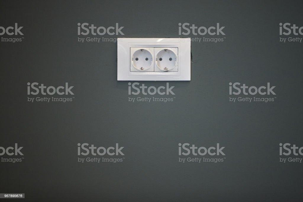 White power socket on a black wall stock photo