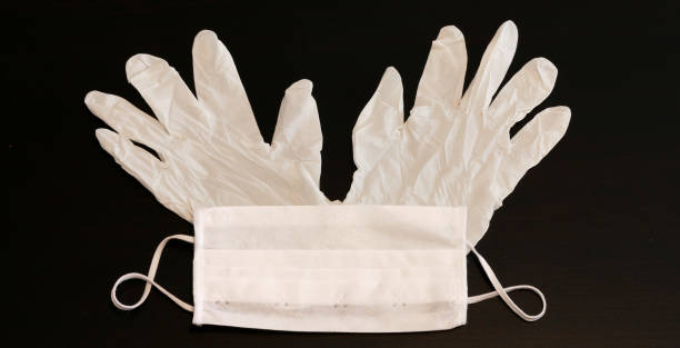 White protective gloves and medical mask stock photo